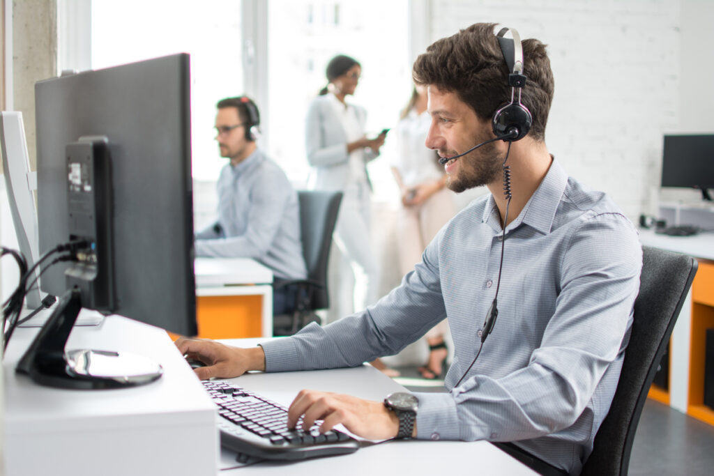 man-wearing-headset-sitting-in-office-at-computer-doing-IT-support-services