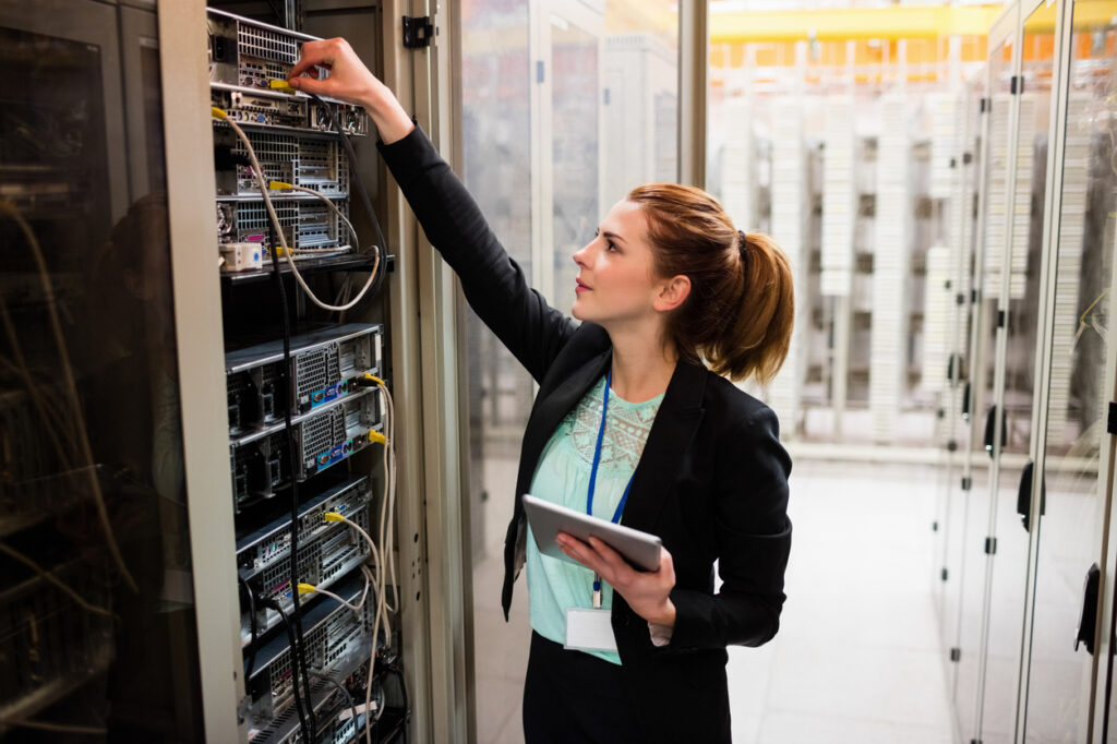 woman-holding-tablet-and-performing-IT-support-task-with-network-cable