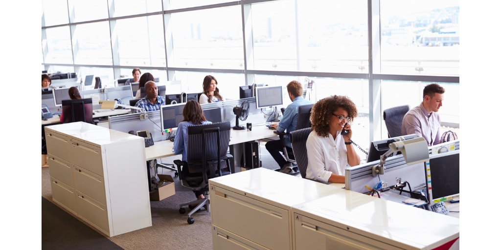 people-sitting-at-desks-in-pairs-next-to-wall-of-windows-in-office-doing-IT-support-outsourcing
