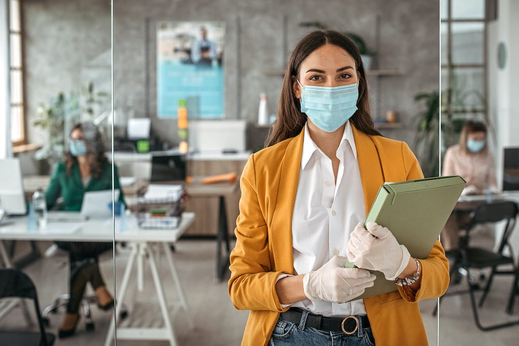 Businesswoman with protective gloves and face mask at office